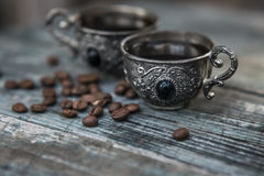 Black coffee in vintage silver cups on wooden background Royalty Free Stock Images