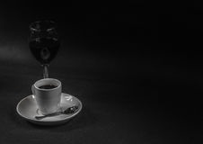 Black coffee in white ceramic cup and red wine in wineglass, dri. Nk set, black and white Royalty Free Stock Photo