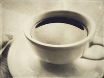 Black coffee in white ceramic cup and saucer in a cafe under window light. stock photography