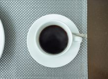 Black coffee in white ceramic cup on table. Top view Royalty Free Stock Photos