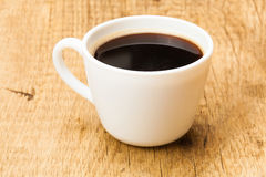Black coffee in white ceramic cup on wooden table - studio shoot Stock Photo