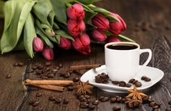 Black coffee in a white cup on a background of red tulips. Rustic style Stock Photo