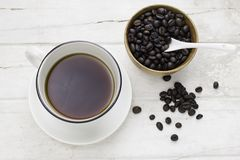 Black coffee in white cup and coffee beans with spoon. On white table. Top view Stock Photos