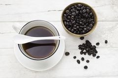 Black coffee in white cup and coffee beans with spoon. Top view Royalty Free Stock Photography