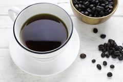 Black coffee in white cup and coffee beans with spoon. Top view Royalty Free Stock Photo
