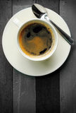 Black coffee in white cup on black and white wood background. Stock Image