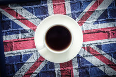 Black coffee in white cup and British flag, Union Jack. Top view Royalty Free Stock Image