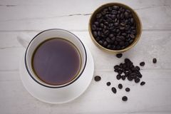 Black coffee in white cup and coffee beans. With vintage filter. Top view Royalty Free Stock Photo