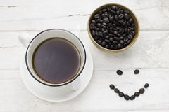 Black coffee in white cup and coffee beans with smiling face. On white table. Top view Royalty Free Stock Photography