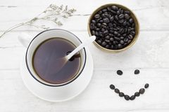 Black coffee in white cup and coffee beans with white spoon and. Dried flower on white table. Top view Stock Image