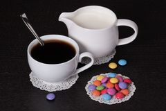 Black Coffee In White Cup, Milk, Candies Stock Photo