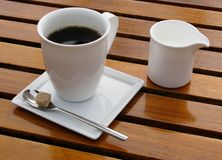 Black coffee in a white cup and milk jar. On a patio table Royalty Free Stock Photos