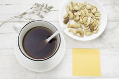Black coffee in white cup and mixed nuts with white spoon. Dried flower and sticky note on white table. Top view Stock Photography