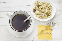 Black coffee in white cup and mixed nuts with white spoon. And dried flower and sticky note on white table. Top view Stock Photo