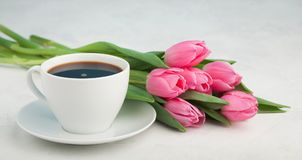 Black coffee in white Cup with pink tulips on light stone background.  Stock Photo
