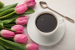 Black coffee in white Cup with pink tulips on light stone background. Top view.  Royalty Free Stock Images