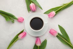 Black coffee in white Cup with pink tulips on light stone background. Top view.  Royalty Free Stock Photo