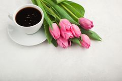 Black coffee in white Cup with pink tulips on light stone background. Top view with copy space.  Stock Photo