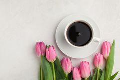 Black coffee in white Cup with pink tulips on light stone background. Top view with copy space.  Royalty Free Stock Photo