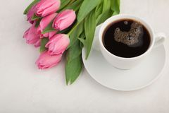 Black coffee in white Cup with pink tulips on light stone background. Top view with copy space.  Royalty Free Stock Photos