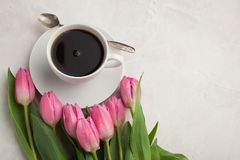 Black coffee in white Cup with pink tulips on light stone background. Top view with copy space.  Stock Photos
