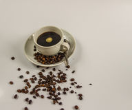 Black coffee in a white cup on saucer with spoon and spilled coffee beans. Artistic decoration Royalty Free Stock Photography