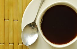Black coffee in white cup with spoon on plate Royalty Free Stock Photos