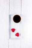 Black coffee in a white cup and two red chocolate hearts on a wooden background. Top view, free space for text. Stock Photos