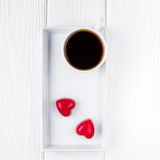 Black coffee in a white cup and two red chocolate hearts on a wooden background. Top view, free space for text. Stock Photo