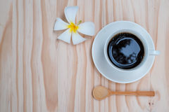 Black coffee in white cup with white plumeria flower on wooden b Stock Photo