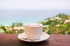 Black coffee, white glass, the background is the sea sky. Royalty Free Stock Images