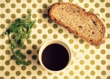 Breakfast with a black coffee, bread and some greens. Black coffee on a white mug and a bread toast Royalty Free Stock Image