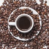 Coffee in a white cup and grains. Black coffee in a white mug and grains royalty free stock photos