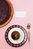 Black coffee whith white card and chocolate cake on pink background Stock Photos