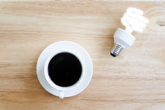 Black coffee on wood table.And brighten lamp. Stock Photography