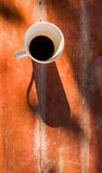 Black coffee on the wood table. Top view of Black coffee in the white coffee cub on the wood table with sun light and shadow Stock Image