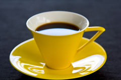 Black coffee in yellow cup and saucer Stock Images