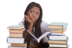 Black college student woman by stack of books. High school or college ethnic African-American female student sitting by the desk with lot of books in class or Royalty Free Stock Images