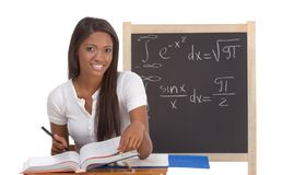 Black college student woman studying math exam. High school or college ethnic African-American female student sitting by the desk at math class. Blackboard with Royalty Free Stock Image