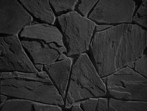 Black color decorative uneven cracked real stone wall Stock Photography