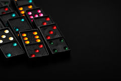 Black color dominoes with colorful dot game pieces Stock Photo