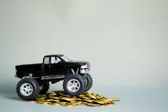 Miniature car pickup truck on stacks of coins on grey background. Black colour of miniature car pickup truck on stacks of coins on grey background with copy Stock Images