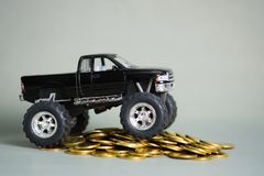 Miniature car pickup truck on stacks of coins on grey background. Black colour of miniature car pickup truck on stacks of coins on grey background with copy Royalty Free Stock Photography