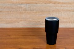 Black colour stainless steel tumbler or cold storage cup on wood. En background Royalty Free Stock Photography