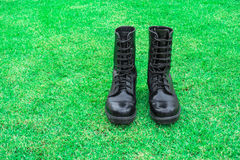 Black combat boot on green grass field. Background Stock Image