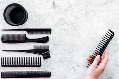 Black combs, brushes for hairdresser work on stone desk background top view mock up Royalty Free Stock Photos