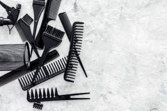 Black combs, brushes for hairdresser work on stone desk background top view mock up Royalty Free Stock Images
