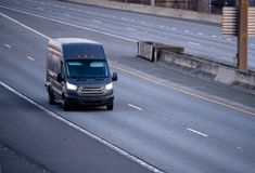 Black cargo mini van running on the multiline road. Black compact commercial useful small business cargo mini van running on the multiline road with turn on royalty free stock photos