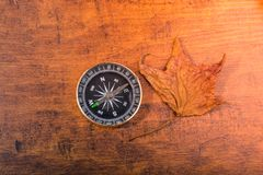 Black compass as  instrument beside a dry leaf. On wooden texture stock images