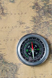 The Black compass on old vintage map, north atlantic ocean, macro background Royalty Free Stock Photography